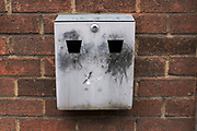 Ash tray which looks like a face on a wall outside. London, UK. Since the smoking ban in public places, these ashtrays have become a common sight as smokers go out to smoke.