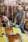 Topping up. Oak barrel aging and fermentation cellar. Chateau Brane Cantenac, Margaux, Medoc, bordeaux, France
