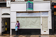 A British woman standing outside of a small shop with paper across the windows in Blandford Forum, United Kingdom.  Like many other small shops in this town, and across the country, it has recently had to close-down due to the financial recession.  The landlords have put it on the market To Let, but are not hopeful that another business will open soon.