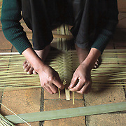 Hands of a woman weaving a bamboo basket in Tang Tien village, Bac Giang province, Vietnam. With Vietnam's growing population making less land available for farmers to work, families unable to sustain themselves are turning to the creation of various products in rural areas.  These 'craft' villages specialise in a single product or activity, anything from palm leaf hats to incense sticks, or from noodle making to snake-catching. Some of these 'craft' villages date back hundreds of years, whilst others are a more recent response to enable rural farmers to earn much needed extra income.