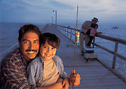 A father holds his son while fishing together at sunrise on a long pier.