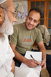 Professional interviewing elderly man at home.