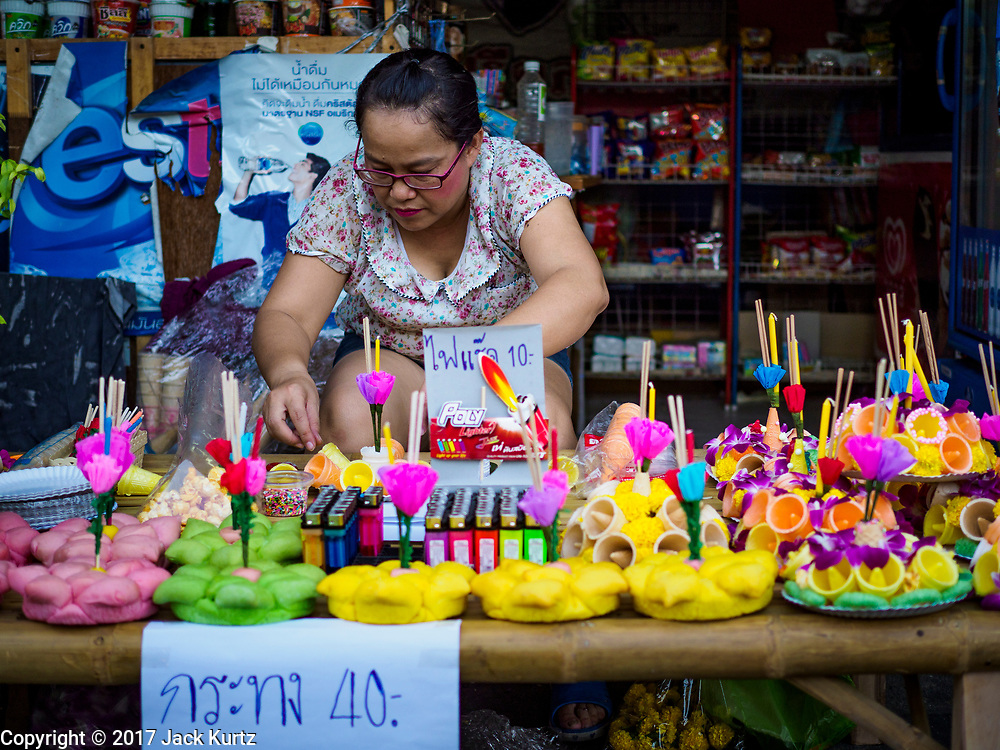 """03 NOVEMBER 2017 - BANGKOK, THAILAND: A woman makes and sells krathongs during Loi Krathong at Wat Prayurawongsawat on the Thonburi side of the Chao Phraya River. Loi Krathong is translated as """"to float (Loi) a basket (Krathong)"""", and comes from the tradition of making krathong or buoyant, decorated baskets, which are then floated on a river to make merit. On the night of the full moon of the 12th lunar month (usually November), Thais launch their krathong on a river, canal or a pond, making a wish as they do so. Loi Krathong is also celebrated in other Theravada Buddhist countries like Myanmar, where it is called the Tazaungdaing Festival, and Cambodia, where it is called Bon Om Tuk.     PHOTO BY JACK KURTZ"""