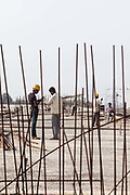 Workers seen through metal cables on a building site on the new footbridge over the Yamuna River, Delhi, India