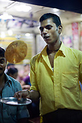 A waiter flips a cooked paratha on a plate at Parawthe Wala restaurant in Old Delhi, India<br /> The parantha is an Indian fried bread, folded and filled with fillings and then fried.<br /> Gali Paranthe Wali or Paranthe wali Gali means the the street of fried bread and name of a narrow street in Chandni Chowk Old Delhi, noted for its series of shops selling paratha