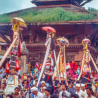 Newari Hindus in Bhaktapur, Nepal, gather to celebrate Gai Jatra (the cow festival) where families honor their dead and march through the city, performing  to encourage their passing to heaven. The towers contain photos and possessions of the deceased.