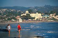 Two women walking on sand at Laguna Beach, Orange County, California