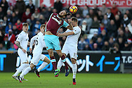 Andy Carroll of West Ham United jumps for a header with Stephen Kingsley of Swansea city.  Premier league match, Swansea city v West Ham United at the Liberty Stadium in Swansea, South Wales on Boxing Day, Monday 26th December 2016.<br /> pic by  Andrew Orchard, Andrew Orchard sports photography.