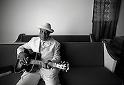 Bishop Dready Manning sits on a pew in his church playing his acoustic guitar.