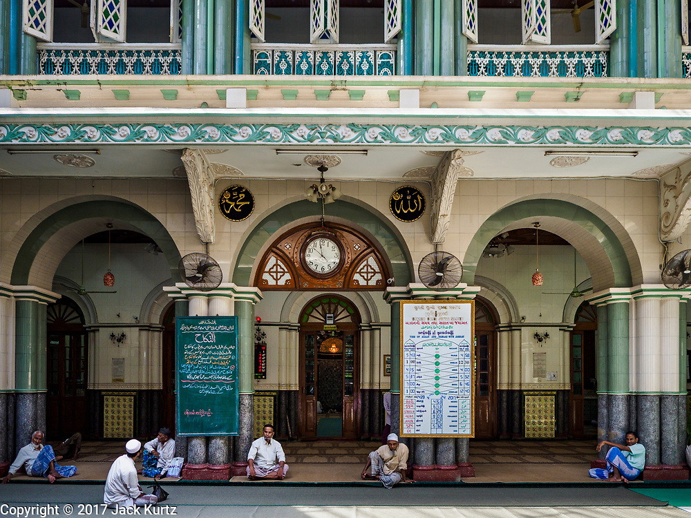 """24 NOVEMBER 2017 - YANGON, MYANMAR: Muslim men wait for Friday midday prayers to start in Surtee Sunni Jumma Mosque in Yangon. Many Muslims in overwhelmingly Buddhist Myanmar feel their religion is threatened by a series of laws that target non-Buddhists. Under the so called """"Race and Religion Protection Laws,"""" people aren't allowed to convert from Buddhism to another religion without permission from authorities, Buddhist women aren't allowed to marry non-Buddhist men without permission from the community and polygamy is outlawed. Pope Francis is to arrive in Myanmar next week and is expected to address the persecution of the Rohingya, a Muslim ethnic minority in western Myanmar. Some Muslims and Christians are concerned that if the Pope's comments take too strong of pro-Rohingya stance, he could exacerbate religious tensions in the country.  PHOTO BY JACK KURTZ"""
