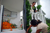 """MEXICO, Veracruz, Tantoyuca, Oct 27- Nov 4, 2009. A mother and daughter work on their family memorial at Tantoyuca's main cemetery. """"Xantolo,"""" the Nahuatl word for """"Santos,"""" or holy, marks a week-long period during which the whole Huasteca region of northern Veracruz state prepares for """"Dia de los Muertos,"""" the Day of the Dead. For children on the nights of October 31st and adults on November 1st, there is costumed dancing in the streets, and a carnival atmosphere, while Mexican families also honor the yearly return of the souls of their relatives at home and in the graveyards, with flower-bedecked altars and the foods their loved ones preferred in life. Photographs for HOY by Jay Dunn."""