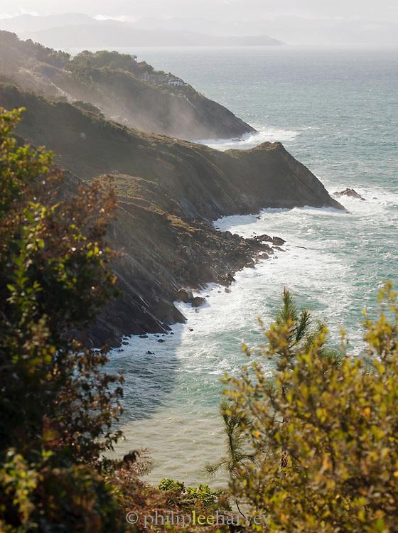 Waves and sea mist crash against cliffs near San Sebastian, Spain