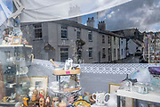 With a reflection of terraced homes in the background, a window of a charity shop that sells bric a brac items, on 3rd October 2021, in Beaumaris, Anglesey, Wales.