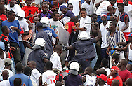 As the situation for the home team deteriorates on the field, police react to a barrage of rocks and trash thrown from the stands.