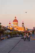 Street in city under a clear sky at sunset and the Granada Cathedral also known as Our Lady of the Assumption Cathedral, Granada, Nicaragua