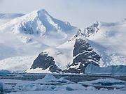 Glacier covered peaks rise steeply from the Southern Ocean at Graham Land, in Antarctica.
