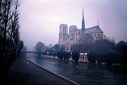 A lone woman walks along a paved walkway beside the Seine river with notre dame cathedral on the other side, 10th May 1980, Paris, France.