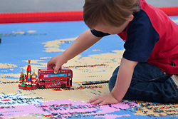 © licensed to London News Pictures. London, UK 13/08/2012. A child playing with a London 2012 double decker bus and replica of the Kremlin Palace on a giant map of the world, measuring 12 by 5 metres, made from over a million Lego bricks by members of public and designed by Duncan Titmarsh for the Festival of the World at Southbank Centre. Photo credit: Tolga Akmen/LNP