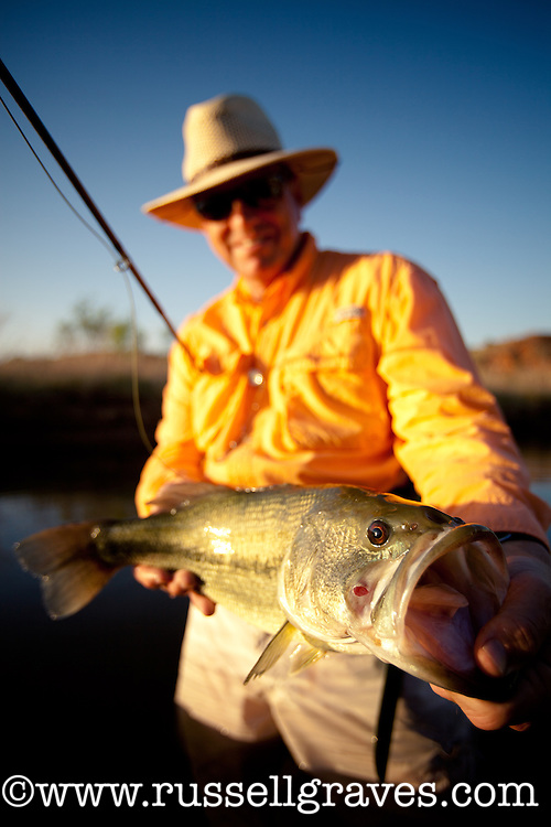 FLY ANGLER FISHING IN THE PEASE RIVER TEXAS AND SHOWING OFF A LARGEMOUTH BASS