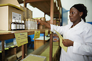 Pharmacist Estelle Balou Line checks stocks of medical supplies in the pharmacy at the Libreville health center in Man, Cote d'Ivoire on Wednesday July 24, 2013.
