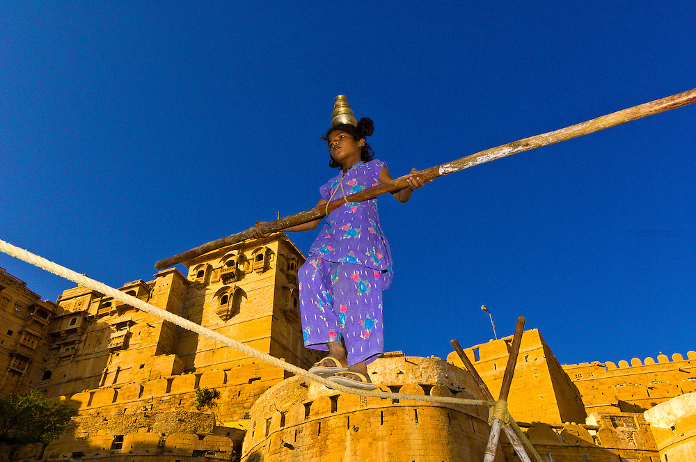 Girl walking a tightrope with the Jaisalmer Fort behind, Jaisalmer, Rajasthan, India