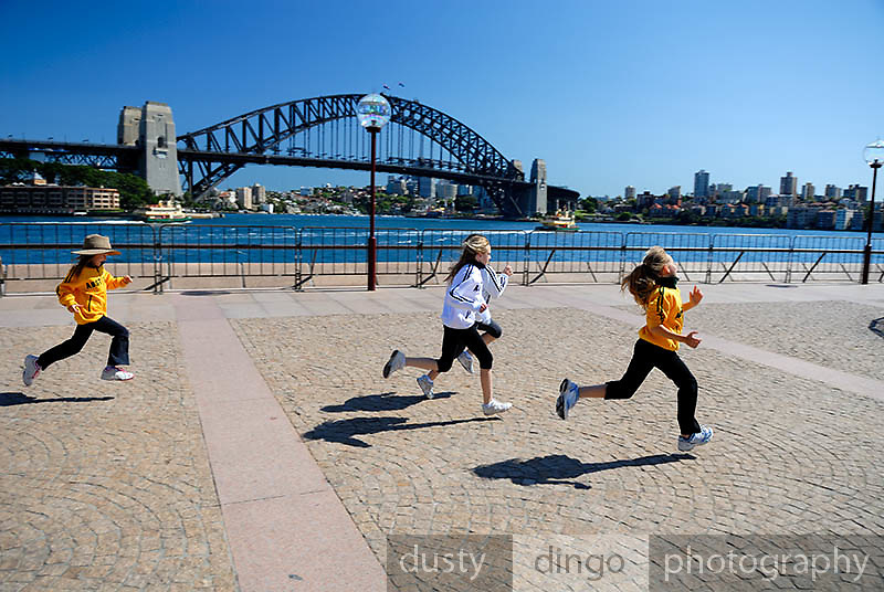 Four girls (one 6 year-old, three 10 year-olds), running on Sydney Opera House concourse, with Sydney Harbour Bridge in background. Circular Quay, Sydney, Australia