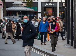 © Licensed to London News Pictures. 15/10/2020. London, UK. Shoppers wear masks outside in Richmond Upon Thames, South West London, which has one of the highest infections rates in the city as the Capital moves to Covid lockdown Tier Two restriction after Heath Minister Matt Hancock announced tougher measure to start midnight on Friday. Millions of people in London will be put into Covid Tier Two lockdown which bans households from mixing inside from midnight Friday as coronavirus levels of infections continue to escalate throughout the UK. Photo credit: Alex Lentati/LNP
