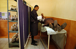 Traditional doctor heats a gold needle to treat joint pains or headaches to a patient at the Trashi Yengtse hospital in Eastern  Bhutan October 15, 2005. (ami Vitale)