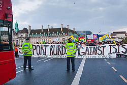 Westminster, October 9th 2014. Police officers watch as protesters block Westminster Bridge as scores of Kurds demonstrate against ISIS and demand that the UK and Turkey assist them in defending themselves against the Jihadist movement.