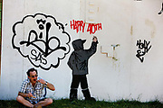 Man eating in front of graffiti in the centre of Shangri-La is the HUB (Hot Utopian Bliss), a town square in the round and a gathering place for the population, Glastonbury Festival 2010