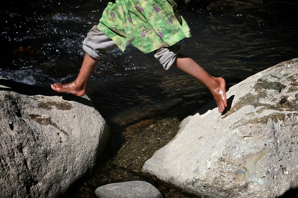 A young girl jumps between rocks in the Cuiko river near the Marlin mine in Guatemala.