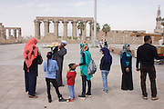 Egyptian tourists buy snacks from a local man in front of the ancient Egyptian columns of Luxor Temple, Luxor, Nile Valley, Egypt.  The temple behind was built by Amenhotep III, completed by Tutankhamun then added to by Rameses II. Towards the rear is a granite shrine dedicated to Alexander the Great and in another part, was a Roman encampment. The temple has been in almost continuous use as a place of worship right up to the present day.
