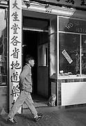 Cat watching man walk down the street in Chinatown, San Francisco