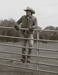 cowboy on a climbing on a fence on a ranch