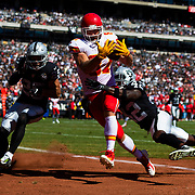 Kansas City Chiefs tight end Travis Kelce (87) catches the ball against Oakland Raiders free safety Karl Joseph (42) and Oakland Raiders free safety Erik Harris (25) during an NFL regular season football game on Sunday, Sep. 15, 2019 in Oakland, Calif. The Chiefs won, 28-3. (Ric Tapia via AP)