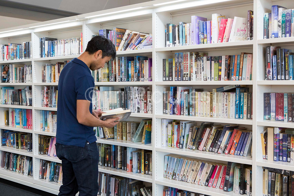 A man stands at one of book shelves with integrated lighting inside the library of the Hive in Worcester, UK. The first fully integrated university and public library in the UK. It houses the county archives and archaeology service, the local history centre and is also a local authority hub. The building is low energy.