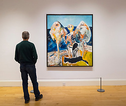 Man looking at painting The Ventriloquist by John Bellamy on display at Scottish National Gallery of Modern Art in Edinburgh, Scotland, United Kingdom