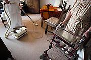 Nederland, Nijmegen, 15-10-2003..Ouderenzorg. Interieurverzorgster, schoonmaakster, stofzuigt de woonkamer van een oudere vrouw in een verzorgingshuis. Verzorging ouderen, bejaarden, klantgerichte zorg. Hulp, werkdruk, aandacht...Foto: Flip Franssen