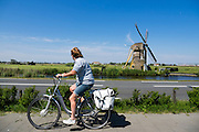 Bij Oegstgeest rijdt een vrouw op een fiets langs een windmolen.<br /> <br /> Near Oegstgeest a woman cycles on a city bike near a wind mill