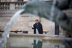 © Licensed to London News Pictures. 23/01/2017. London, UK. A man photographs the fountains in Trafalgar Square, which have frozen over this morning. Thick fog has covered London, whilst temperatures drop to -2 degrees celsius. Photo credit : Tom Nicholson/LNP