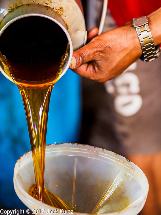 15 MARCH 2017 - KHOKANA, NEPAL: Workers pour freshly made mustard oil at the Gaabu Jyaasha Oil Mill in Khokana, Nepal. The mustard oil is made by hand with local grown mustard seeds. The seeds are roasted then pressed in a large press operated by a hand screw. The first pressing of oil is sold in local markets around Khokana and shipped to grocery stores in Kathmandu. The seeds are pressed a second time in a mechanical press, and that oil is sold for use in oil massages. The dry remains are sold to local farmers for livestock and chicken feed or composting material. The mill is family owned and has been making mustard oil for seven generations. Mustard oil is used for cooking in North India, Eastern India, Nepal, Bangladesh and Pakistan. In Bengal, Orissa, Assam and Nepal, it is the traditionally preferred oil for cooking. It is illegal to import mustard oil into the US because of possible health issues with the oil.           PHOTO BY JACK KURTZ