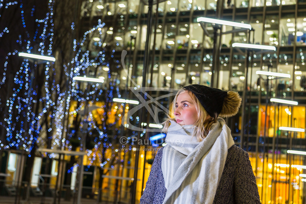 Canary Wharf, London, January 16 2018. A woman admires the synchronised movement of lights in 'Abstract' by Collectif Coin of France at the Winter Lights festival at Canary Wharf in London which features over 30 spectacular light installations at interactive art. © Paul Davey