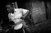 """NAIROBI, KENYA - MARCH 17, 2010: A Kenyan youth plays a drum on the streets of Kibera slum. Nearby, graffiti painted the famous Kenyan artist Solo7 is a reminder of the recent post-election violence. <br /> <br /> Various grassroots initiatives led by youth have begun to improve the quality of life for those living in the direst of conditions, and young people of different tribes are using gardening, waste removal, education and athletics to encourage their peers toward a self-respecting and self-sustaining community. Termed """"youth groups"""" on the street, these initiatives could represent the future of long-term socioeconomic development in Kenya while laying the groundwork for a more peaceful election in 2013. During the post-election violence of 2007 and 2008, impoverished youth in Kenya were routinely bribed by the nation's political elite to carry out acts of violence in their communities. Idleness among the youth, combined with the nation's history of tribal rivalries, were cited as a key factors to the violence, culminating in the deaths of over 1,200 Kenyans and the displacement of over 600,000. Since the violence, many youth have begun to seize active roles in the reform of their nation. In 2010 United States Ambassador Michael Ranneberger said he sensed """"a sea change of attitude"""" among youths, """"a tidal wave below the surface. The youth have woken up."""""""