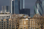Tall financial properties in the City of London including the Swiss Re building, far right, (aka the Gherkin) rise above modern riverside residential apartments and the terrace of former dock officials' houses (designed by Daniel Asher Alexander) at Wapping Pierhead, built in 1811–13, on 17th January 2020, in London, England.