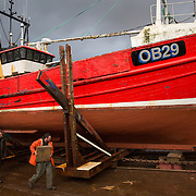 Mallaig Boatyard. Head boatbuilder/ foreman Graham MacKenzie secures the Ranger onto the cradle.  Picture Robert Perry 9th April 2016<br /> <br /> Must credit photo to Robert Perry<br /> FEE PAYABLE FOR REPRO USE<br /> FEE PAYABLE FOR ALL INTERNET USE<br /> www.robertperry.co.uk<br /> NB -This image is not to be distributed without the prior consent of the copyright holder.<br /> in using this image you agree to abide by terms and conditions as stated in this caption.<br /> All monies payable to Robert Perry<br /> <br /> (PLEASE DO NOT REMOVE THIS CAPTION)<br /> This image is intended for Editorial use (e.g. news). Any commercial or promotional use requires additional clearance. <br /> Copyright 2014 All rights protected.<br /> first use only<br /> contact details<br /> Robert Perry     <br /> 07702 631 477<br /> robertperryphotos@gmail.com<br /> no internet usage without prior consent.         <br /> Robert Perry reserves the right to pursue unauthorised use of this image . If you violate my intellectual property you may be liable for  damages, loss of income, and profits you derive from the use of this image.