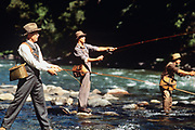 """BOZEMAN, MT - AUGUST:  Tom Skerritt (Reverend Maclean), Craig Sheffer (Norman Maclean) and Brad Pitt (Paul Maclean) fly fish the Gallitin River during the filming of """"A River Runs Through It"""" in 1991. (Photo by John Kelly/Getty Images)"""