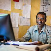 INDIVIDUAL(S) PHOTOGRAPHED: Tesfa Gebru. LOCATION: Mecha Health Center, Bahir Dar, Ethiopia. CAPTION: CBHI Health Officer Tesfa Gebru smiles from behind his computer.