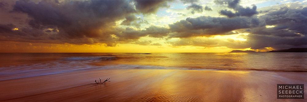 A panoramic photograph of a sunrise over Yorkey's Beach, Cape Grafton visible on the right, with driftwood in the foreground.<br /> <br /> Limited Edition Print
