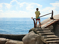 A tourist stands on a footbridge on Koh Tao island in Thailand, Southeast Asia