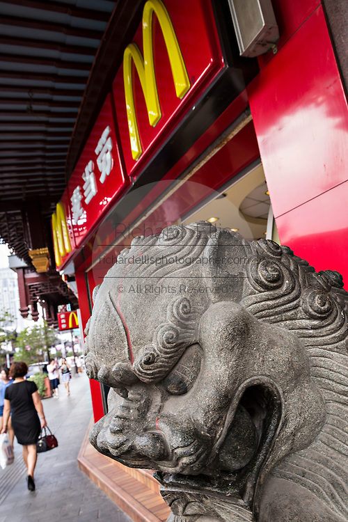 A McDonald's restaurant with a Chinese lion statue in Yu Gardens bazaar Shanghai, China